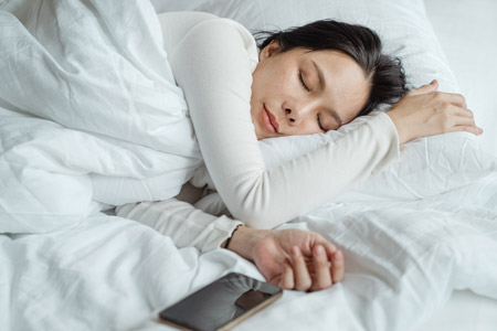 Woman sleeping with her phone in the bed