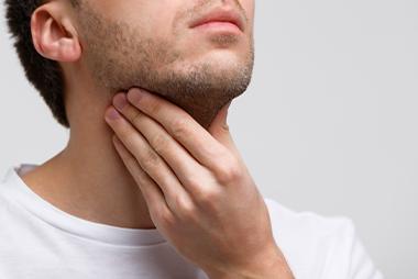 Man holding sore throat