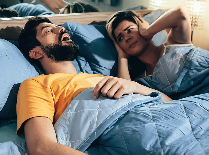 A man snoring with a woman covering her hears