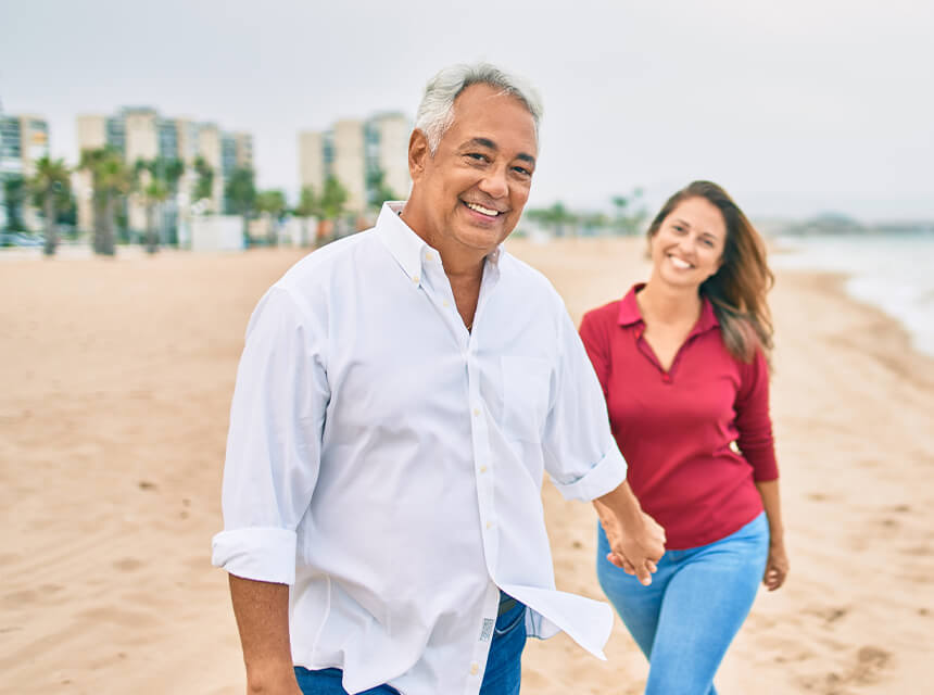 Couple smiling and holding hands while walking on the beach