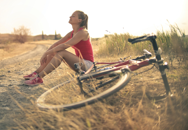 Woman smiling next to a bike outside